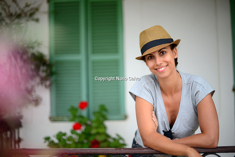 Attractive young woman poses in front of traditional house, Ibiza, Balearic Islands, Spain