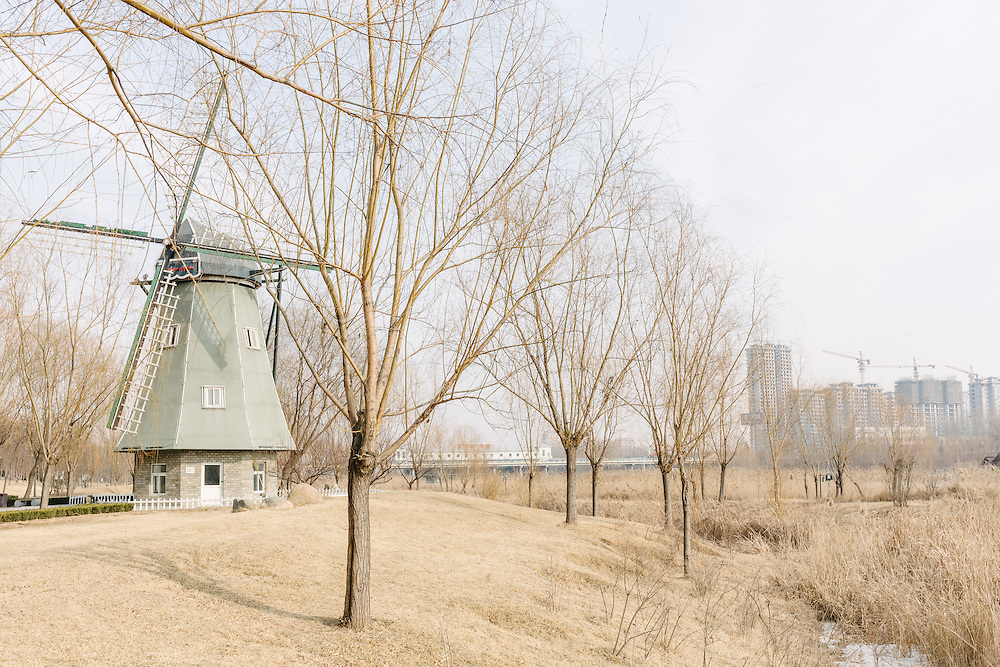 """A wind turbine, disguised as a scenic windmill set along the river by the new industrial zone hailed as the """"Solar Valley"""" of Dezhou."""