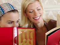 Two young women sitting on sofa holding books close up