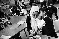A girl whispers into teacher's ear in the classroom at Malik Academy. Massachusetts, 2011