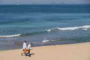 Musicians walk along Ipanema beach early morning in Rio de Janeiro, Brazil.