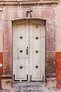 A traditional hacienda style painted wooden door on a historic home in San Miguel de Allende, Mexico.
