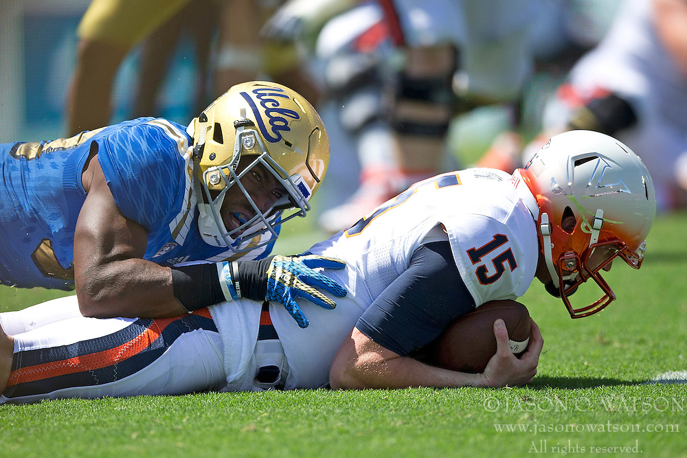 PASADENA, CA - SEPTEMBER 05:  Quarterback Matt Johns #15 of the Virginia Cavaliers is sacked by linebacker Deon Hollins #58 of the UCLA Bruins during the first quarter at the Rose Bowl on September 5, 2015 in Pasadena, California. The UCLA Bruins defeated the Virginia Cavaliers 34-16. (Photo by Jason O. Watson/Getty Images) *** Local Caption *** Matt Johns; Deon Hollins