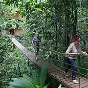 Two visitors crossing a wooden bridge linking their bedroom to the living room on one of the main treehouses of Finca Bellavista