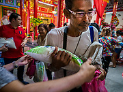 04 SEPTEMBER 2017 - BANGKOK, THAILAND: A man picks up a sack of rice and bottles of cooking oil at Chaomae Thapthim Shrine. About 1,000 people came to the shrine for the annual food distribution. Staples, like rice and cooking oil, are donated to the shrine throughout the year and donated to poor people from the communities around the shrine. Food distributions like this are a tradition at Chinese shrines in Bangkok and a common way of making merit for the people who donate the staples.     PHOTO BY JACK KURTZ