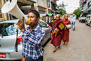 "13 JUNE 2013 - YANGON, MYANMAR:   A man with a bullhorn announces Buddhist monks walking down a street in Yangon soliciting alms and donations. Most men in Myanmar join the ""Sangha"" (clergy) at least once in their life. Some stay monks for just a few weeks, others for year and a few make it a life time commitment. Yangon, formerly Rangoon, is Myanmar's commercial capital and used to be the national capital. The city is on the Irrawaddy River and has a vibrant riverfront.  PHOTO BY JACK KURTZ"