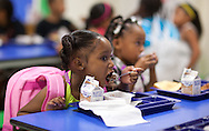 Torian Julius, 7, 1st grade, of Cedar Rapids, eats her breakfast in the cafeteria on the first day of school at Polk Elementary School, 1500 B Avenue NE, in Cedar Rapids on Thursday morning, July 21, 2011.