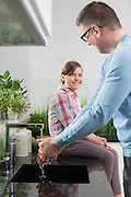 Smiling girl looking at father washing hands in kitchen