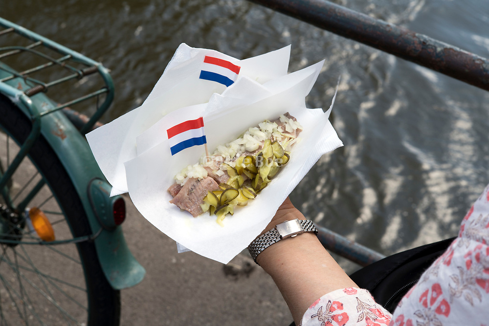 raw herring with the traditional Dutch flag pickles and unions in Amsterdam