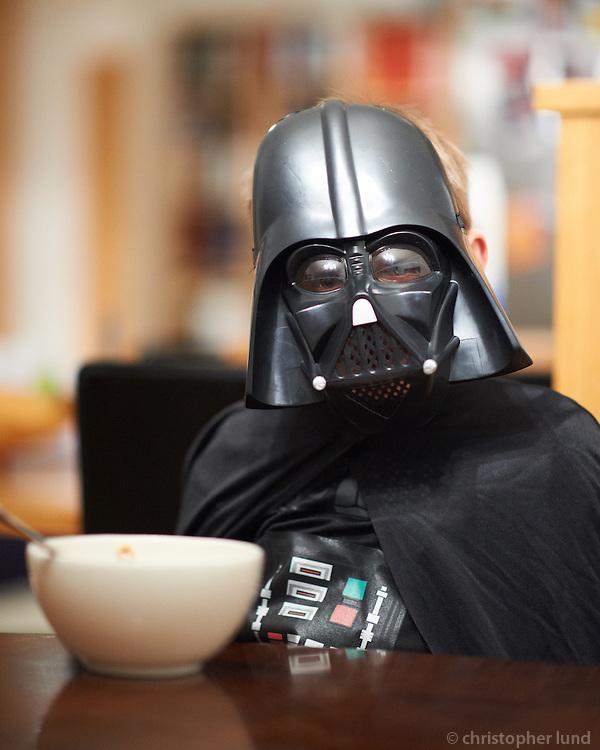 Young boy (8) dressed as Darth Vader from Star Wars eating breakfast at home. Svarthöfði fær sér morgunmat. Ari Carl klár í öskudaginn 2012.
