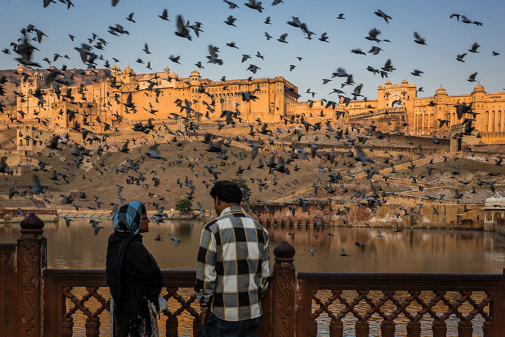 A couple talks as a flock of pigeons scatters near Amber Fort