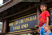 A young boy is standing near a stylish sign tht marks the northern border with Tachilek, Burma (Myanmar) in Mae Sai, (Sae) Thailand.