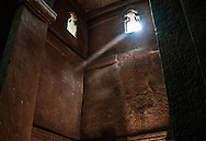 A ray of sunlight slices through the dark interior of Bet Giyorgis (St. George's Church) perfect in its minimalism.  These stone walls are carved out of the volcano mountain itself, one piece of stone, inseparable from the mountain.  Legend has it that King Lalibela (r 1181 - 1221) was poisoned by his half-brother and travelled to heaven while in coma, where God showed him a city hewn from stone and commanded him to return to earth to build a new Jerusalem out of stone.