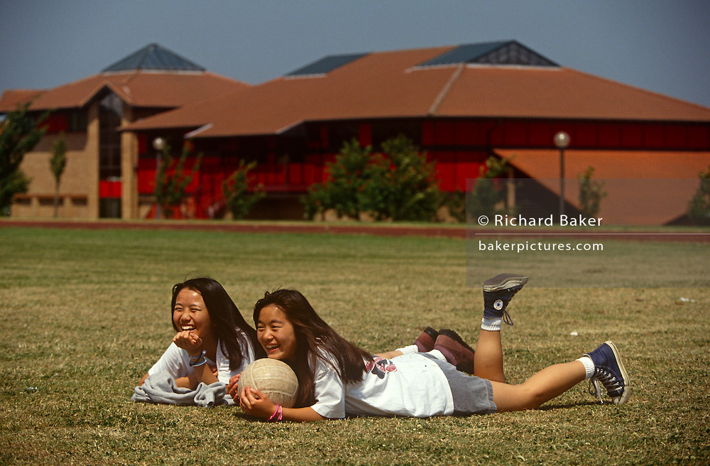 Teenage girl students sit on the sports field at the Gyosei International Japanese School, a boarding school for Japanese ex-pats opened in 1987 in Willen Park, Milton Keynes, England. The two girls lie on their fronts on clipped grass in the middle of their sports field, the main school building seen in the beckground. Holding on to a football, they're laughing at the antics of unseen school friends, they enjoy the summer's afternoon in the English Midlands.