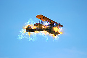 Digitally enhanced side view image of a burning biplane in flight