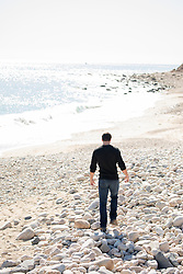 man walking on a rocky beach in the Fall