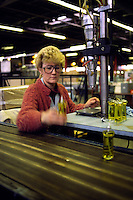 Woman working on the bottling line in a perfume factory....