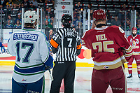 REGINA, SK - MAY 19: Referee Quincy Evans stands at centre ice with Tyler Steenbergen #17 of Swift Current Broncos and Jeffrey Truchon-Viel #25 of Acadie-Bathurst Titan at the Brandt Centre on May 19, 2018 in Regina, Canada. (Photo by Marissa Baecker/CHL Images)