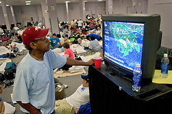 29 August, 2005. New Orleans, Louisiana.<br /> Hurricane Katrina hits New Orleans. Residents of the Hyatt Hotel are moved to the conference rooms where a man watches the approaching storm in sleeping quarters now occupied by thousands of apprehensive residents and trapped tourists. <br /> Photo; Charlie Varley.