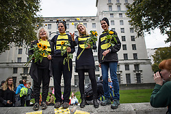 © Licensed to London News Pictures. 07/10/2019. London, UK. Extinction Rebellion protestors dressed as bees, stand together on a wall opposite Downing Street in Westminster . Activists will converge on Westminster blockading roads in the area for at least two weeks calling on government departments to 'Tell the Truth' about what they are doing to tackle the Emergency. Photo credit: Ben Cawthra/LNP