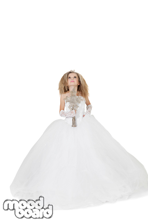 Bride girl in wedding gown holding crucifix looking up over white background