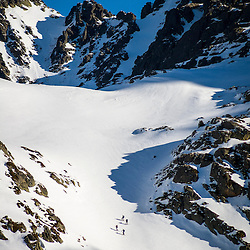Four skiers are dwarfed by the mountains in Andorra.