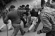 Violent clashes between pro and anti Mubarak in Tahrir Square. <br /> Beaten pro Mubarak supporter caught by anti demonstrators is taken away.
