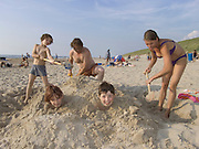 family at the beach having fun by digging in two boys