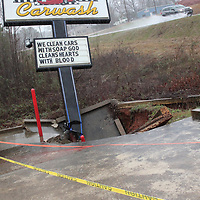 A section of the parking lot of My Classic Carwash, located alongside Highway 278 in Amory, is taped off after torrential rain caused a sinkhole. A drainage ditch flows near the area of the sinkhole.