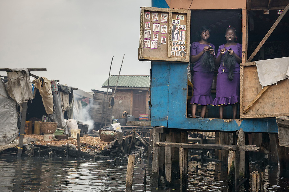 Two women, dressed in purple and holding weaves, stand in the doorway of a hair and beauty saloon, one of several such waterside establishments in Makoko.