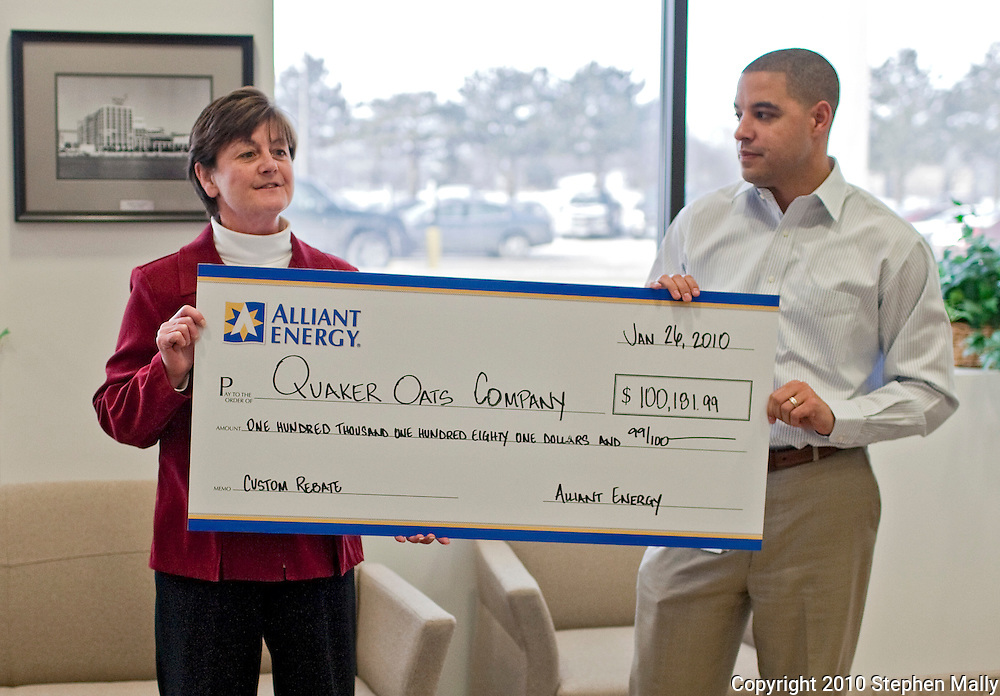 Quaker Oats' Kay Driscoll (left) speaks after reciving a check from Alliant Energy's Chad Wiltz (right) at Quaker Oats in Cedar Rapids, Iowa on Tuesday January 26, 2010. (Stephen Mally for Quaker Oats)