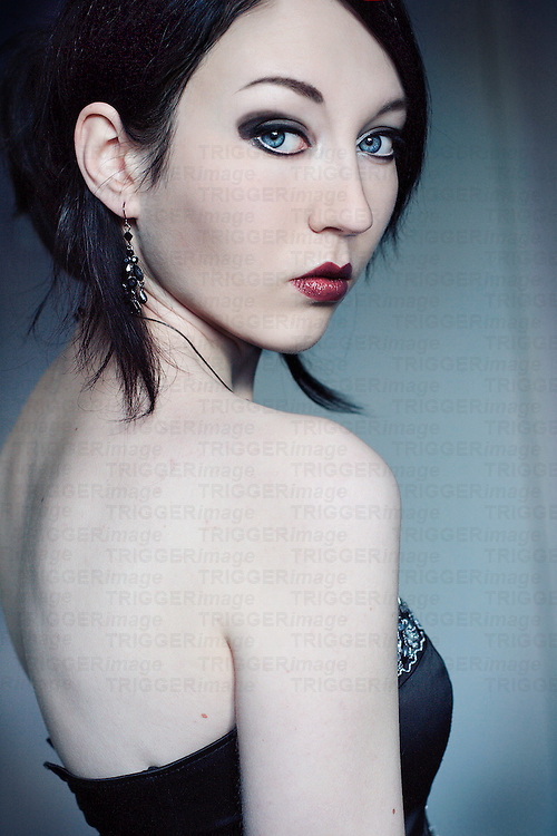 Portrait of a young woman with black hair blue eyes and pale skin looking into the camera over her shoulder with simple background.