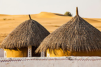Thatched roof huts and sand dunes at Resort Rawla, Thar Desert, Rajasthan, India.