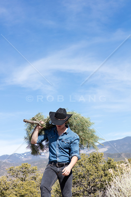 cowboy carrying a freshly cut Christmas Tree over his shoulder by a mountain range