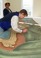 M J Davis works on hand painting repair work to the Lakeport Opera House drape curtain with Brenda Kean director of the Historical Society looking on Tuesday afternoon.  (Karen Bobotas/for the Laconia Daily Sun)