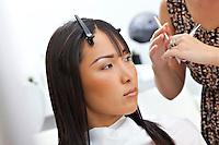 Hairstylist giving a haircut to Asian woman