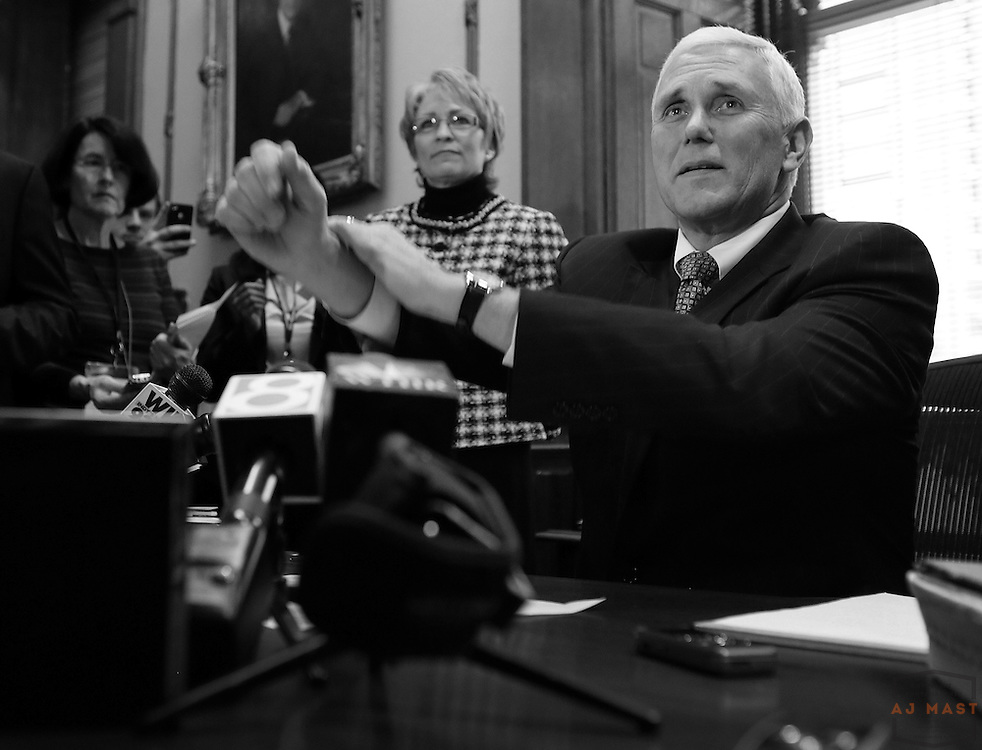 Indiana Governor Mike Pence signs executive orders in his office during a media avalability following his inauguration events in Indianapolis, Monday January 14,2013. (Photo by AJ Mast)