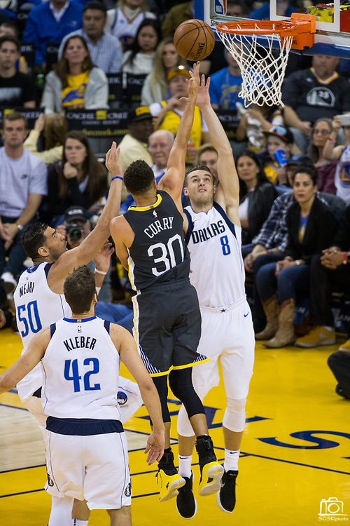 Golden State Warriors guard Stephen Curry (30) takes the ball to the basket against Dallas Mavericks guard Kyle Collinsworth (8) at Oracle Arena in Oakland, California, on February 8, 2018. (Stan Olszewski/Special to S.F. Examiner)