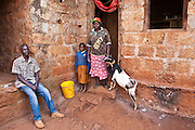 Nancy stands outside her home with her children Peter and Margaret.  Nancy is disabled and unable to work to support her family. AFCIC (Action for children in conflict) have supplied her with goats and a chicken coup to help her support her family.