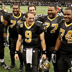 December 26, 2011; New Orleans, LA, USA; New Orleans Saints quarterback Drew Brees (9) poses for a photo with his offensive line following a win over the Atlanta Falcons where Brees broke Dan Marino's single season record for passing yardager during the fourth quarter of a game against the Atlanta Falcons at the Mercedes-Benz Superdome. Mandatory Credit: Derick E. Hingle-US PRESSWIRE