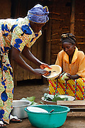 Women cook a clean dishes outside their home in the village of Bukunda, DRC on Thursday August 5, 2010..