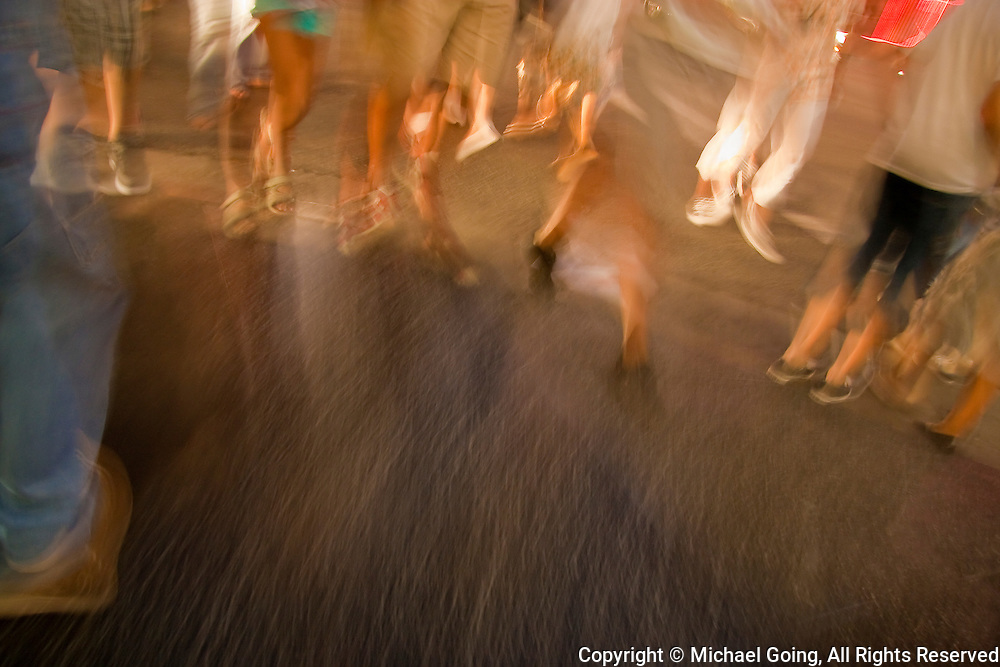 Group of casually dressed pedestrians with motion blur of legs and feet