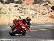 Adam Pratt on a 2004 Honda CBR-1000RR with sport touring luggage rounding a corner in southern Utah