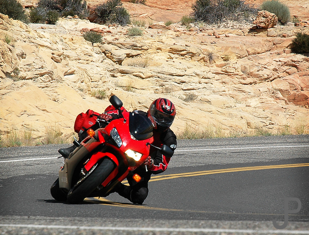 Adam Pratt on a 2004 Honda CBR-1000RR with sport touring luggage rounding a corner in southern Utah