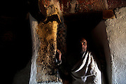 """A Priest stands in the shadows of his ancient rock-hewn church. Occupying a high plateau and bordering with Eritrea in the very north of Ethiopia lies the ancient Province of Tigray. It is an area widely considered to be the fulcrum of Ethiopian culture with towns dated to before the birth of Christ. Distinctively different from the rest of Ethiopia, strongly Orthodox Christian and culturally proud, Tigray is a mountainous and rocky region dotted with ancient churches carved in to sandstone cliffs. Filling these churches are old religious manuscripts and Bibles safe-guarded by protective Priests. Its remoteness has protected the culture as well as the religious sanctuaries that have been described as """"the greatest of the historical-cultural heritages of the Ethiopian people"""". But now Tigray is at a crossroads. Improved infrastructure has led to an opening up of even the remotest towns and villages. Signs of modernity such as internet cafes and cell phones are increasingly being used by younger Tigraians dressed in jeans and T-shirts. Yet the Church remains an ancient and powerful institution which protects its ancient customs creating scenes that haven't changed since Biblical times.."""