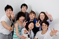 Group portrait of young friends showing peace sign