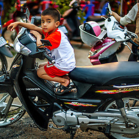 Jan 7, 2013 - Raised on two wheels, the children of Cambodia are moved like everyone else on motorbikes here in the town of Sihanoukville.<br /> <br /> Story Summary: Amidst the feverish pace of Phnom Penh&rsquo; city streets, a workhorse of transportation for people and goods emerges: Bicycles, motorcycles, scooters, Mopeds, motodups and Tuk Tuks roam in place of cars and trucks. Almost 90 percent of the vehicles roaming the Cambodian capital of almost 2.3 million people choose these for getting about. Congestion and environment both benefit from the small size and small engines. Business is booming in the movement of goods and and another one million annual tourists in Cambodia&rsquo;s moto culture.