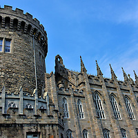 Record Tower at Dublin Castle in Dublin, Ireland <br /> In 1204, King John of England commissioned a stronghold to defend the city against potential Norman attacks. The Record Tower on the left, finished in 1228, is the oldest surviving building of the original Dublin Castle.  It was used as a prison and is now the Garda or Police Museum. On the right is the Chapel Royal. The Gothic Revival structure by architect Francis Johnston was finished in 1814.  In 1943, it became the Church of the Most Holy Trinity.  Since 1922, the 11 acre castle property houses government offices.  However, sections such as the State Apartments and two museums are available for public tours.
