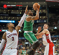 Oct 10, 2014; Toronto, Ontario, CAN;  Boston Celtics guard Marcus Thornton (4) shoots between forward James Johnson (3) and center Tyler Hansbrough (50)  in the fourth quarter at Air Canada Centre. Raptors won 116-109. Mandatory Credit: Peter Llewellyn-USA TODAY Sports