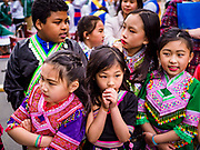 "29 APRIL 2017 - MINNEAPOLIS, MINNESOTA: Children from Thailand watch entertainers at the Songkran Uptown celebration. Several thousand people attended Songkran Uptown on Hennepin Ave in Minneapolis for the city's first celebration of Songkran, the traditional Thai New Year. Events included a Thai parade, a performance of the Ramakien (the Thai version of the Indian Ramayana), a ""Ladyboy"" (drag queen) show, and Thai street food.     PHOTO BY JACK KURTZ"